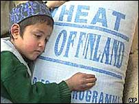 2002: Afghan boy with bag oif wheat distributed by World Food Programme