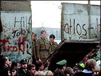 East German guards watch as section of Berlin wall comes down, 1989