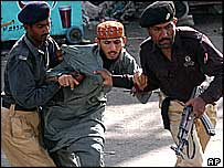 Police restrain man during protest against Shia mosque bomb, Karachi, June 2004