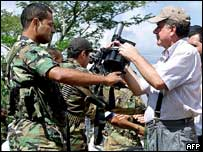 AUC member hands weapon to government peace commissioner, Dec 2004