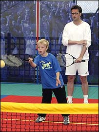 Friends star Matthew Perry watches a youngster play Mini Tennis