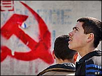 Youths pass symbol of Communist Party, Chisinau, 2005