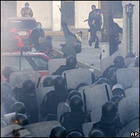 Riot police clash with protesters throwing missiles