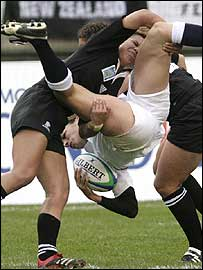 England's Sue Day is turned upside tackle by New Zealand's Linda Itunu