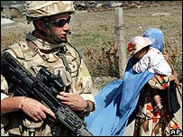 A British soldier from Nato patrolling next to an Afghan woman in Kabul