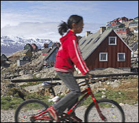 Inuit girl cycles past houses on Uummannaq island, northern Greenland