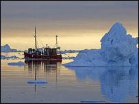 Trawler passes Arctic icebergs in Ilulissat ice fjord, Greenland