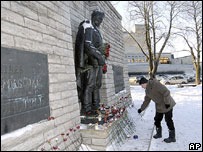 Man lays flower at Soviet war memorial, Tallinn