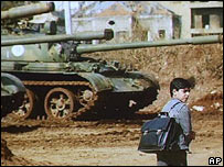 A child walks past some tanks on the way to school in Beirut in 1990