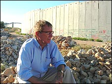 Peter Taylor sits by the Israeli wall