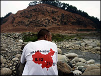 A man wearing a T-shirt showing the date and time of the quake sits on a damaged hillside in Luoshui on 8 June 2008