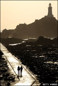 A couple walk on the causeway leading to Corbiere lighthouse Jersey