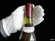 A rare bottle of wine being displayed by a Christie's employee at an auction preview