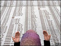 A Bosnian Muslim woman prays at the memorial wall at the Potocari Memorial Center near Srebrenica on 22 July 2008