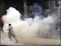 Kashmiri Muslim protesters run for cover as tear gas shell explode near them during a march in Srinagar 11 August