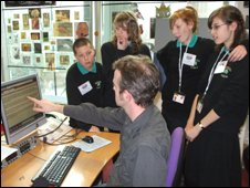 Mentor and students gather round computer