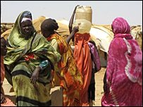 People who have fled the conflict in Darfur collect water at a camp