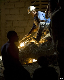 Rescuer uses a welding torch to cut through metal (7 November 2008)