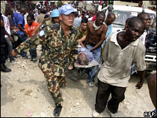 UN personnel help carry an injured person (7 November 2008)