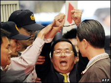 Chen Shui-bian (centre) raises his handcuffed-hands outside the prosecutor's office in Taipei (archive image)