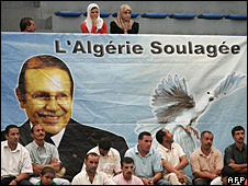 Algerians sit under a poster of Abdelaziz Bouteflika with a dove, September 2007