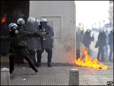 A fire bomb burns next to riot police in Thessaloniki on 7 December 2008