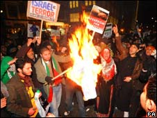 Protesters burn a flag outside the Israeli Embassy in London