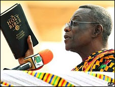 John Atta Mills holding a Bible during his swearing-in ceremony