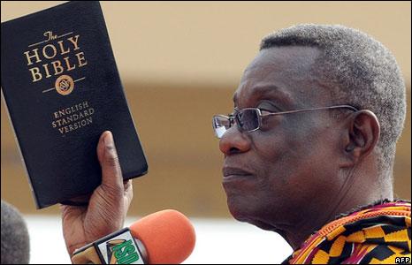 John Ata Mills holding a Bible
