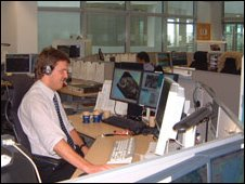 Man working in office at two computers, with rest of office in the background