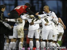 Swansea players celebrate after beating Portsmouth in the FA Cup