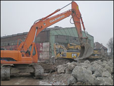 Excavators clear the rubble on the old Gdansk shipyard site
