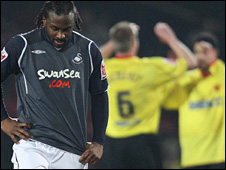 Jason Scotland hangs his head as Watford celebrate their second goal