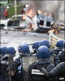 French policemen stand in front of burning cars in Pointe-a-Pitre, Guadeloupe, 18 February 2009 