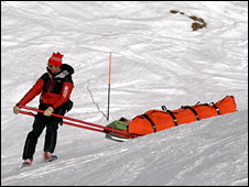 Ski patrol member transports an injured skier