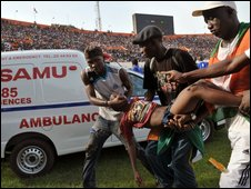 Supporters carry an injured person on at Felix Houphouet-Boigny stadium in Abidjan on 29 March 2009