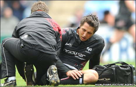Gavin Henson is helped by the Ospreys medical staff after injuring his ankle