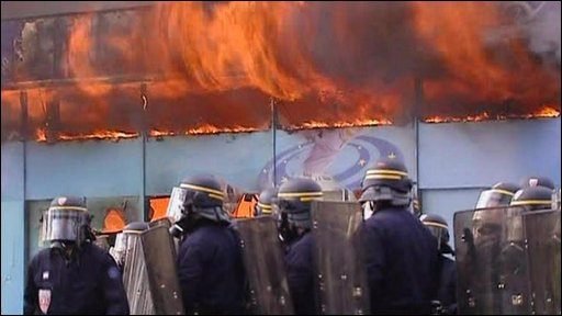Police outside a building set alight by protesters