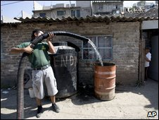 A city worker delivers a resident's weekly water supply in a poor part of Mexico City, 9 April 