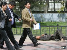 Executives in suits walk past a homeless man in Beijing (file photo: 2007)