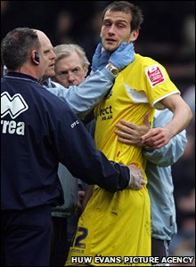 Roger Johnson receives treatment before being taken to hospital following a controversial clash with Claude Davis