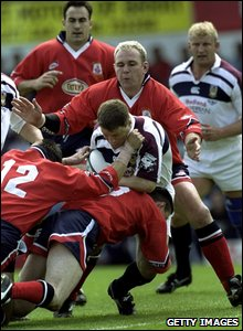 1999: Swansea centre Scott Gibbs is wrapped up by Scott Quinnell and the Llanelli defence during their 37-10 SWALEC Cup Final win at Ninian Park