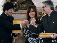 Presidents Evo Morales (L) of Bolivia and Fernando Lugo (R) of Paraguay, shake hands while Argentine President Cristina Fernandez de Kirchner applauds in Buenos Aires on April 27, 2009