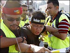 A protester is arrested outside the Perak state assembly in Ipoh, Malaysia