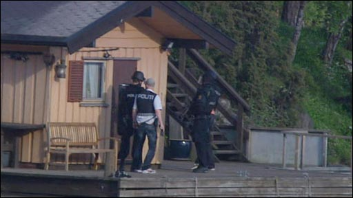 Armed police surround a building in the Oslo suburb