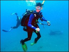 A diver races to Tina Watson, seen in the background of a diving photograph