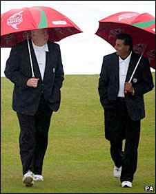 The umpires walk out with their umbrellas as the rain falls in Durham