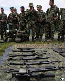 Soldiers stand by weapons and ammunition seized from rebels on 11 May