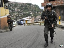 Police officers patrol a poor neighborhood in Medellin, Colombia, 9 April 2009
