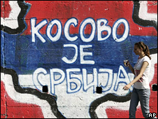 "Woman walks past a mural saying ""Kosovo is Serbia"" in Belgrade (21 May 2009)"